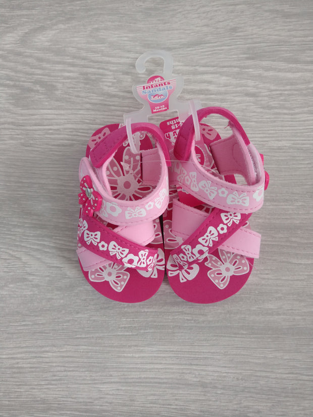 Pink sandals with bow detail and velcro straps.