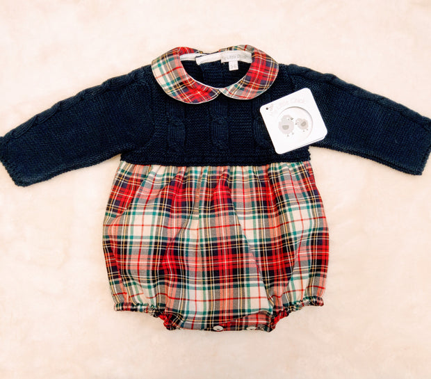 Navy knitted and tartan romper, with matching tartan peter pan collar. Cable knit detailing to sleeves and bodice, with button fastenings to legs and back.  Why not match with navy tights?