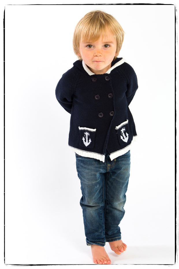 Nautical style double breasted knitted cotton pramcoat, with hood and long sleeves so perfect for cooler weather.   Contrasting white anchor detail to front pockets, white trim to the hood, sleeves and pockets.   100% cotton, cool wash.   Now only available in 12-18 months.