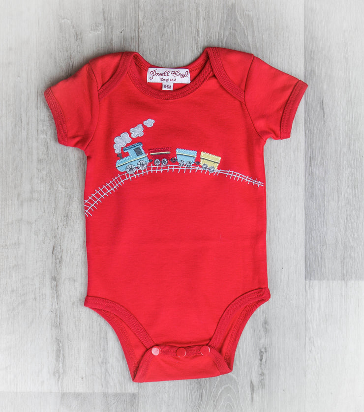 Red cotton baby grow with embroidered train design.   Envelope neck and poppers to crotch. Capped sleeves.   100% cotton. Machine washable.   Why not match with red train hooded jumper, bib and jumpsuit?