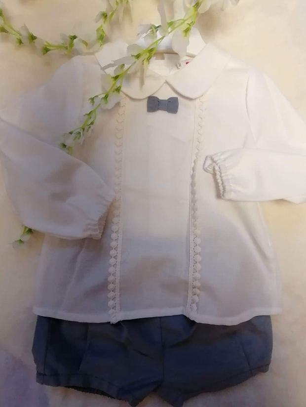Long sleeved off-white shirt with collar and lace trimmed front panel, small bow which matches the light grey fine needlecord shorts. Shirt buttons down back.   Looks good with knee socks!