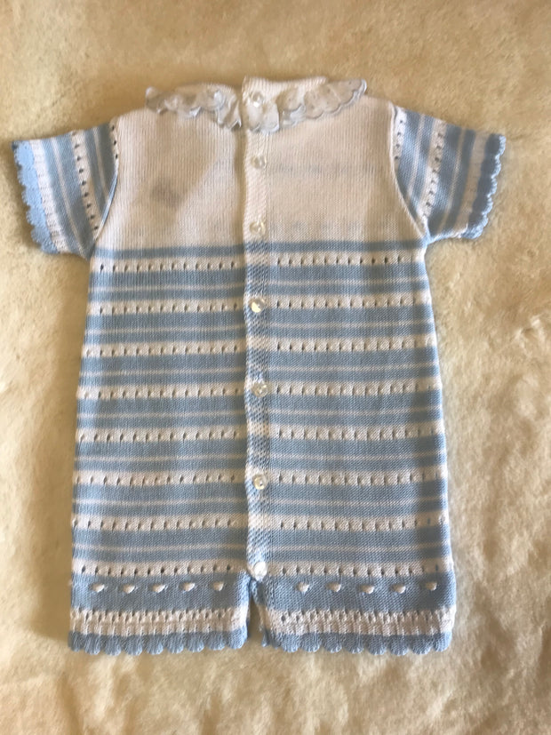 Looking for something a little different?  This blue and white stripe knitted romper has scalloped edging to sleeves and legs, frill detail to neckline.   Easy to undress baby as it has button fastenings to back and legs!   Machine washable.