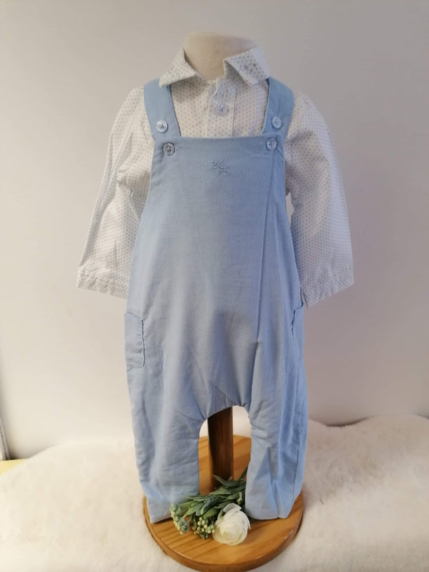 Sky blue fine cord dungarees which crossover at back, patch pockets to side, dungarees even have two sets buttons so great as baby is growing.   Collared white shirt with blue dots with embossed silver stars to collar, shirt buttons down front.