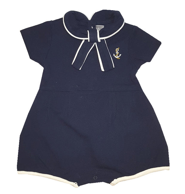 "Let's go sailing!  Adorable navy pique romper, with button fastening to the back and poppers to the legs. Peter pan collar with neck tie and embroidered ""nautical"" motif to front.  100% Cotton"