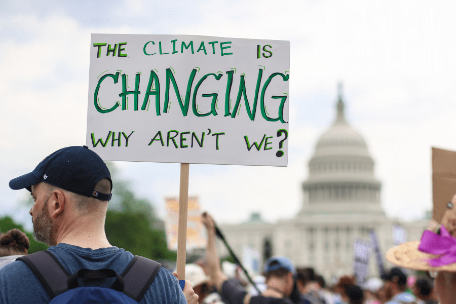 An individual who is holding a climate change sign.