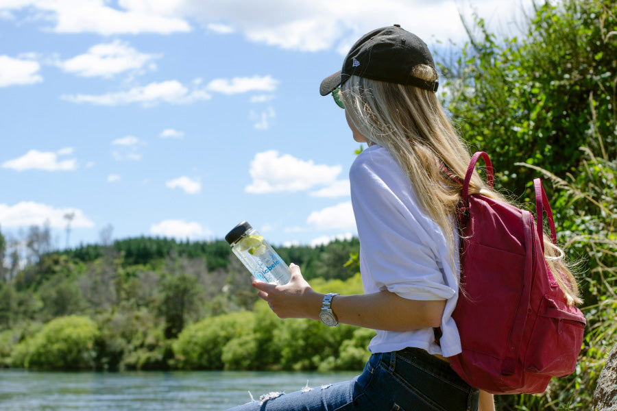 Woman holding bottle of water outdoors. Consume more with less is part of the sustainability in the workplace method.