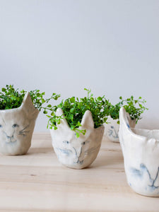 Four pinched pottery kitty planters with hand-drawn face