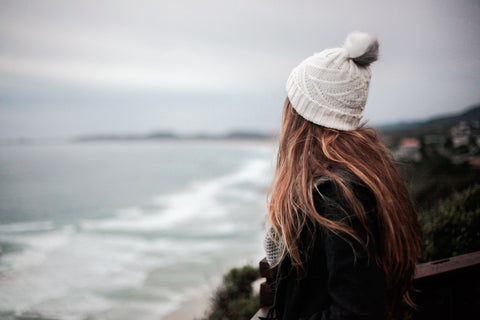 Girl standing by beach cold weather long hair