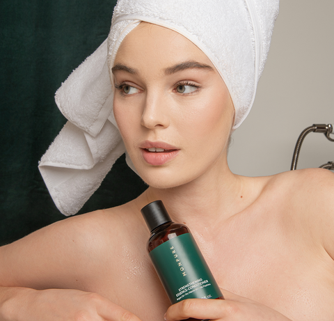 Image of woman holding a bottle of hair strengthening conditioner