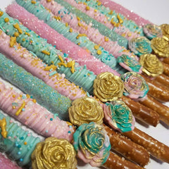 light pink and mint boho theme chocolate covered pretzels with gold fondant roses and light pink and turqouise fondant roses. Topped with coordinating color drizzles and custom sprinkle mix.