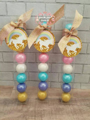 Gumball favor tubes featuring an assortment of pinkl, purple, gold, light blue and white gumballs in a unicorn theme with pastel unicorn rainbow and gold favor tags and pink and gold ribbon.