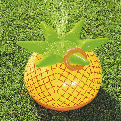 Inflatable pineapple sprinkler game on a green lawn