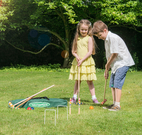 Two children playing croquet on a grass lawn