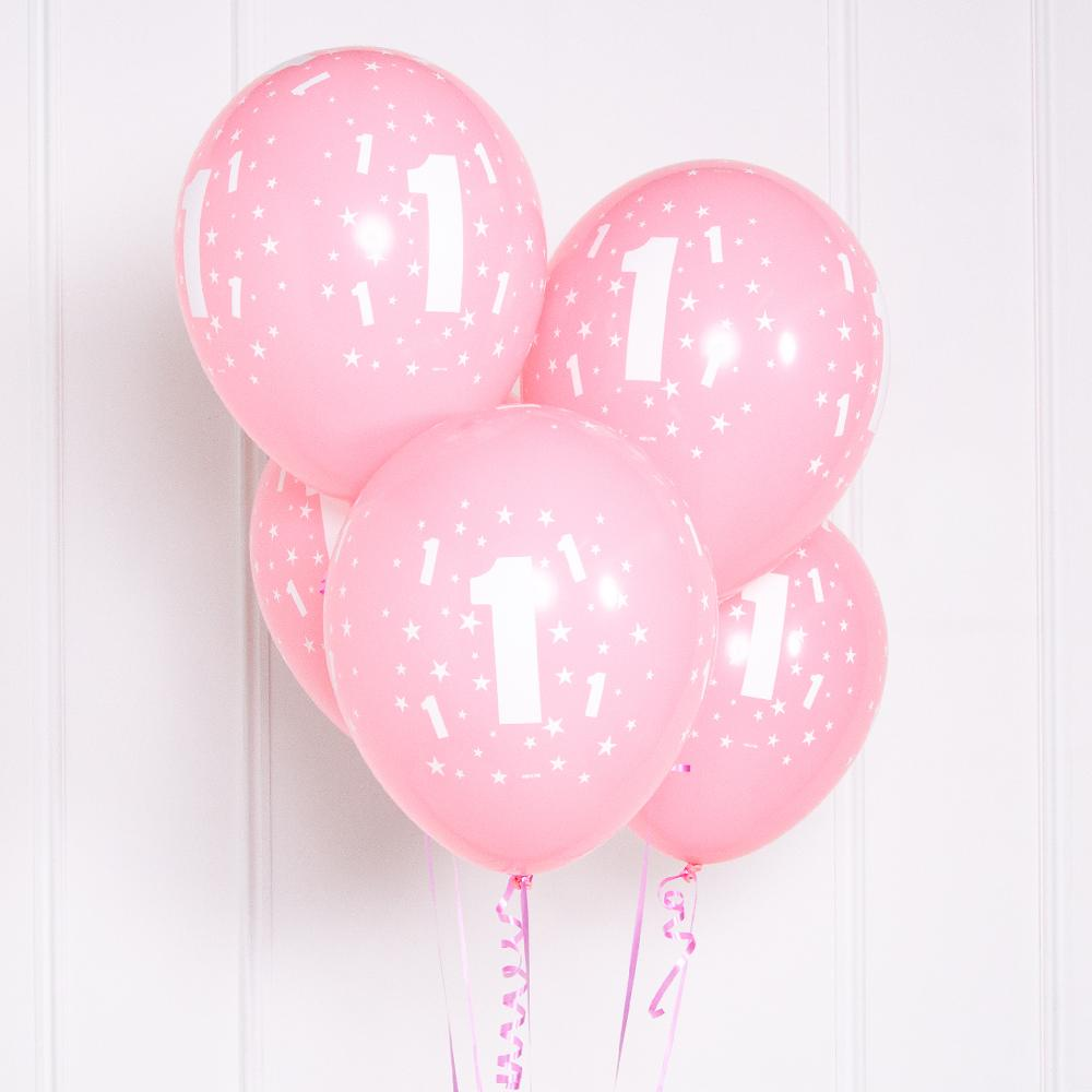 A bunch of pink latex party balloons with a 1st birthday print on the side