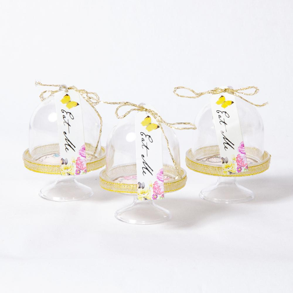 "3 transparent Alice in Wonderland party cakedomes and an ""Eat Me"" label"