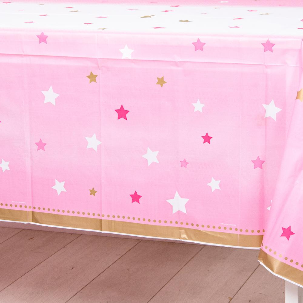 A pastel pink party table cover with pink and white stars for a 1st birthday event