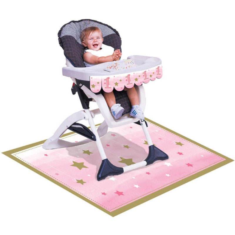 A baby in a high chair decorated with pink 1st birthday party supplies