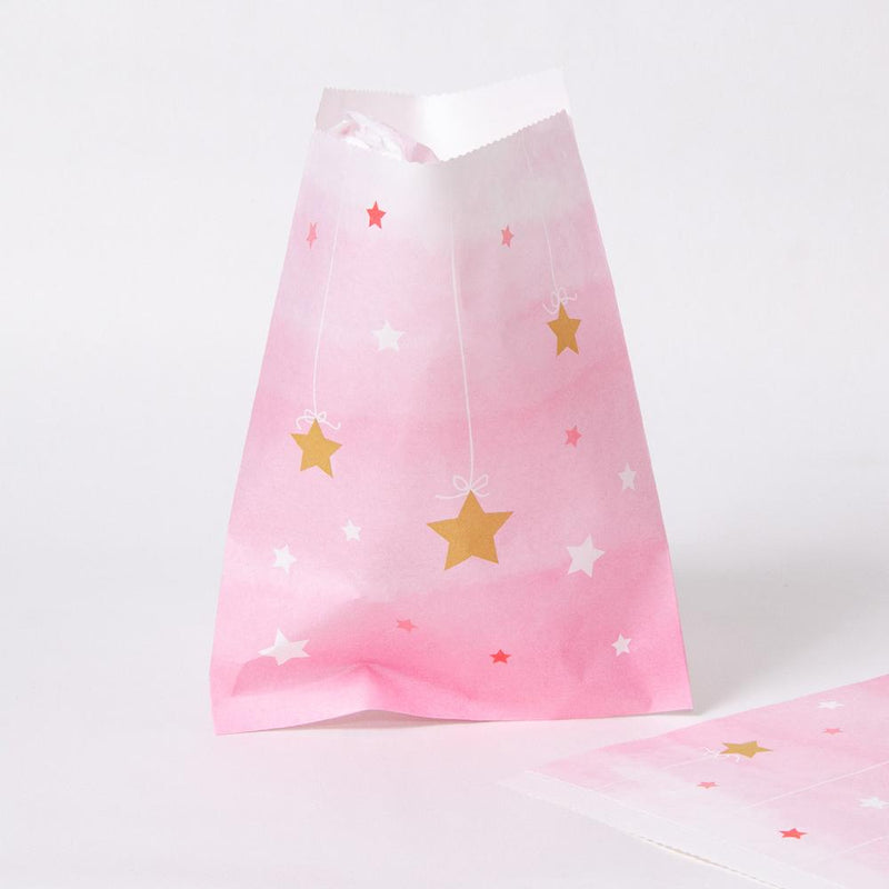 A pink pastel-coloured party bag featuring gold and white stars