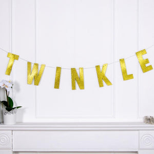 "A 1st birthday banner with a gold foil phrase that says ""TWINKLE"""