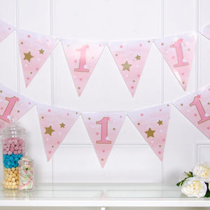 A pink 1st birthday party garland with gold foil stars