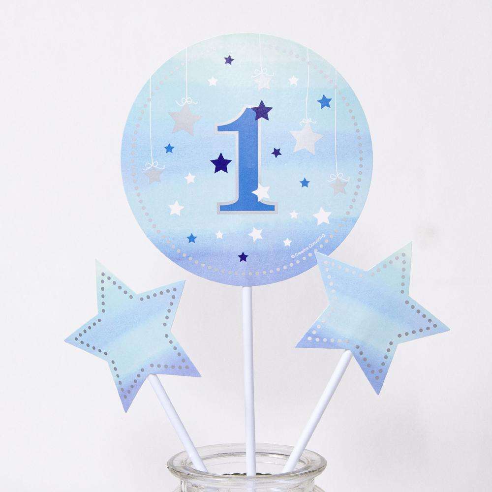 A blue 1st birthday table centrepiece with star shapes and a big round number 1 design