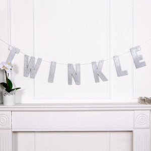 "A silver foil 1st birthday banner saying ""Twinkle"""
