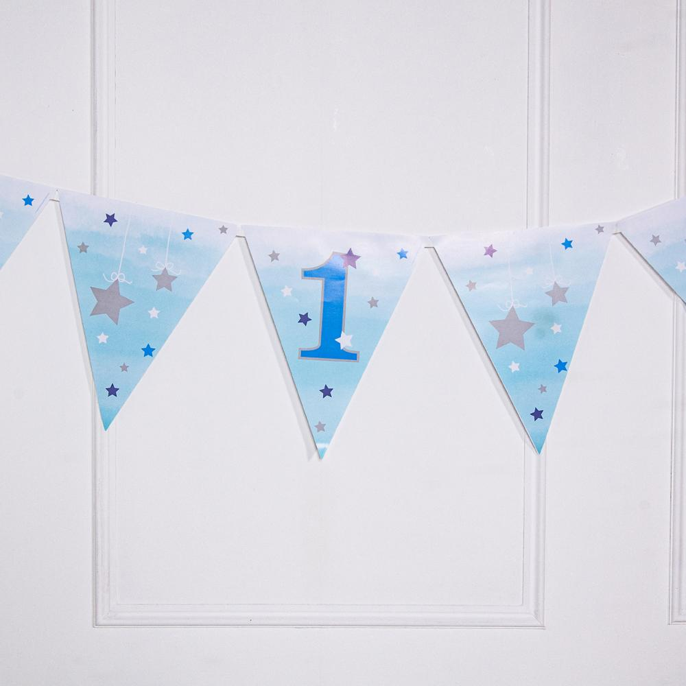 A 1st birthday party bunting banner with pastel blue pennants and shiny silver stars