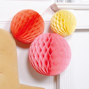 3 soft colour paper pom poms in a pink, orange, and yellow colour