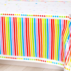 A rainbow-themed party tablecover with a stripy design
