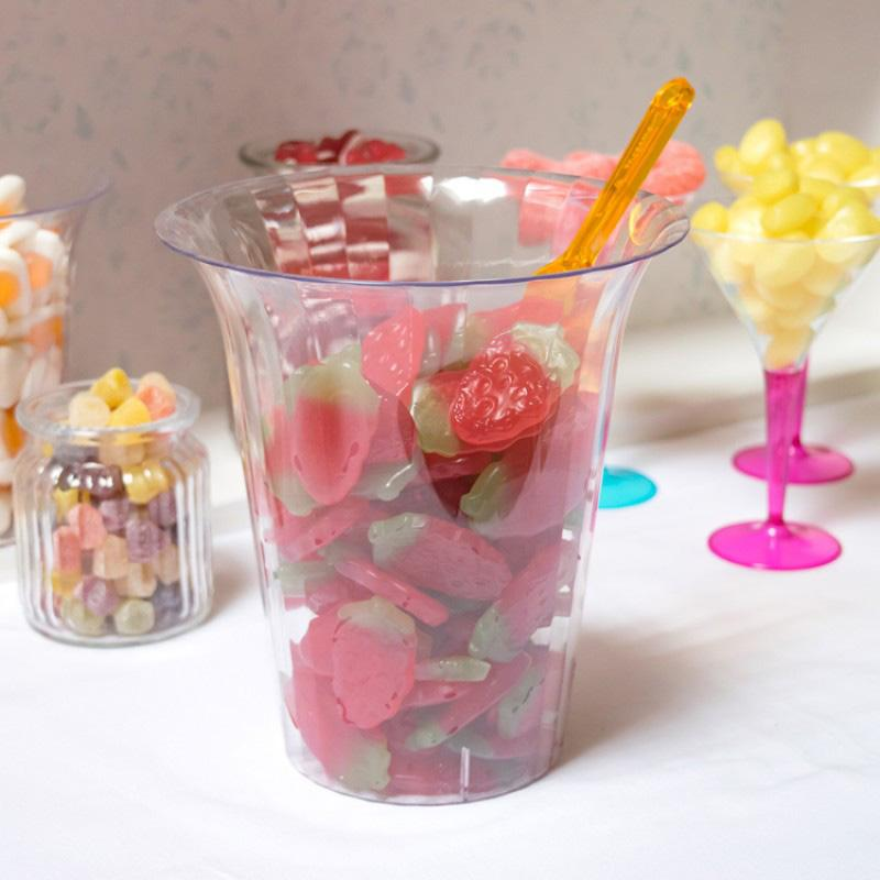 A large transparent plastic party jar filled with strawberry sweets
