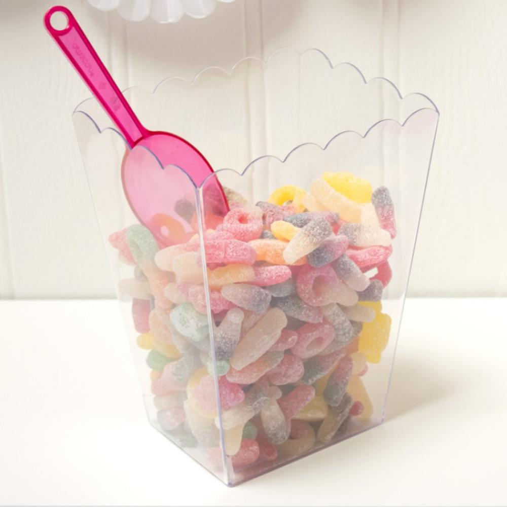 A large, scalloped sweet jar filled with a variety of party sweets