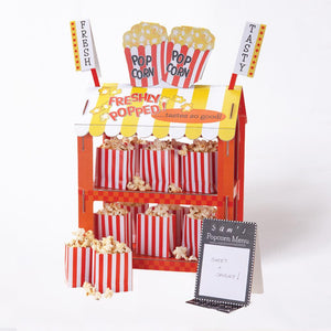 A red and white striped party stand with popcorn and hotdogs