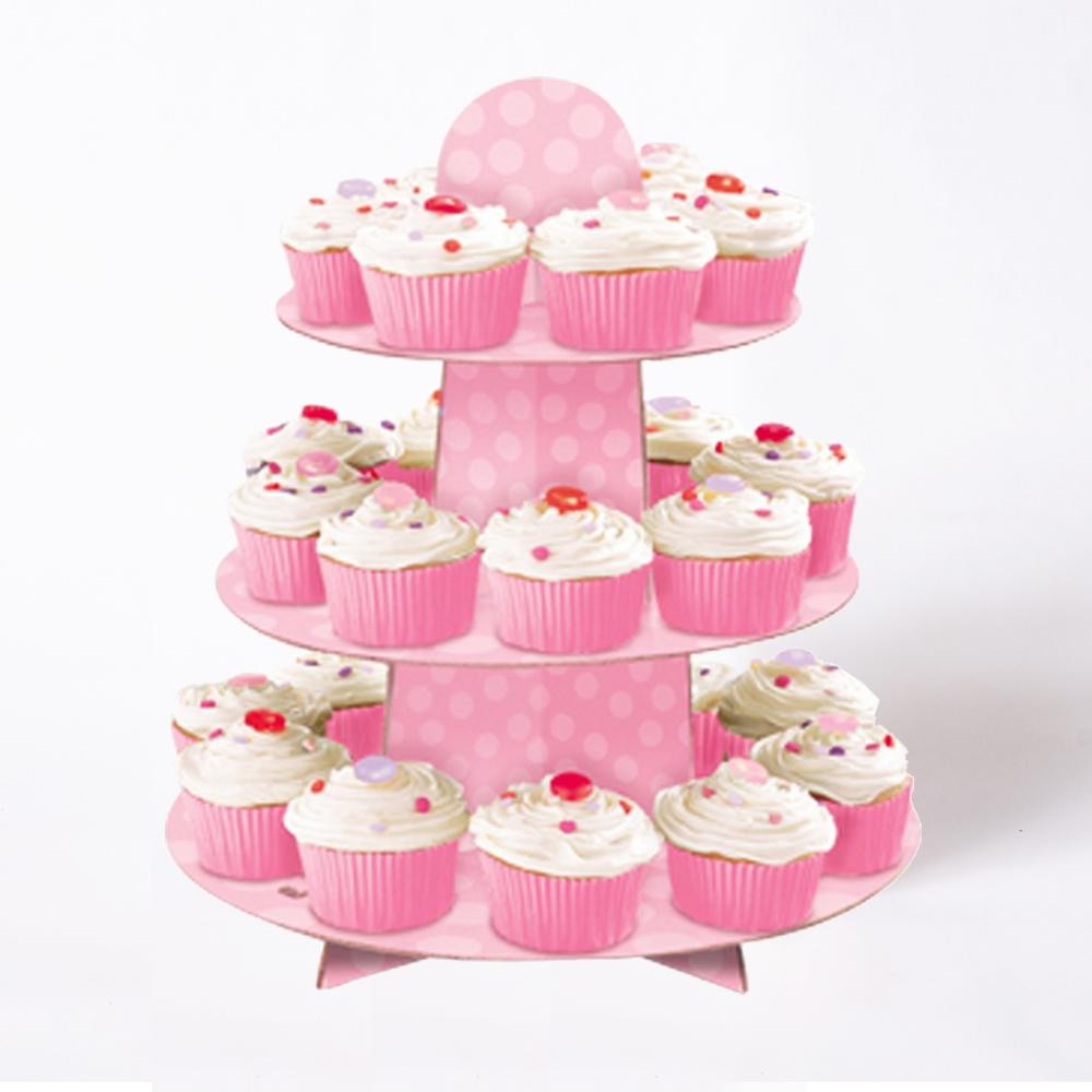 A pale pink polkadot cake stand covered in cupcakes