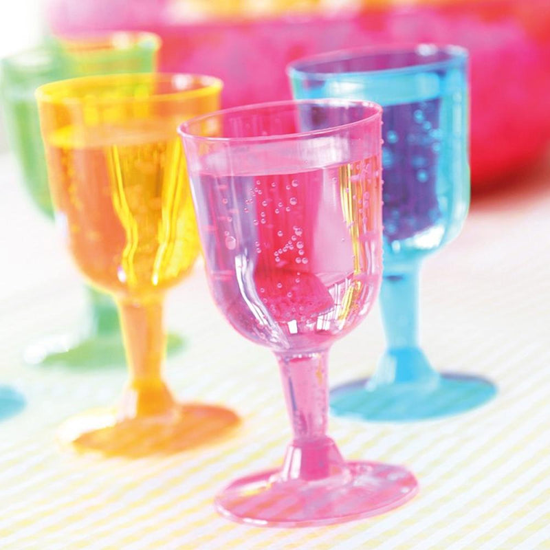 A set of coloured plastic wine glasses filled with a fizzy drink
