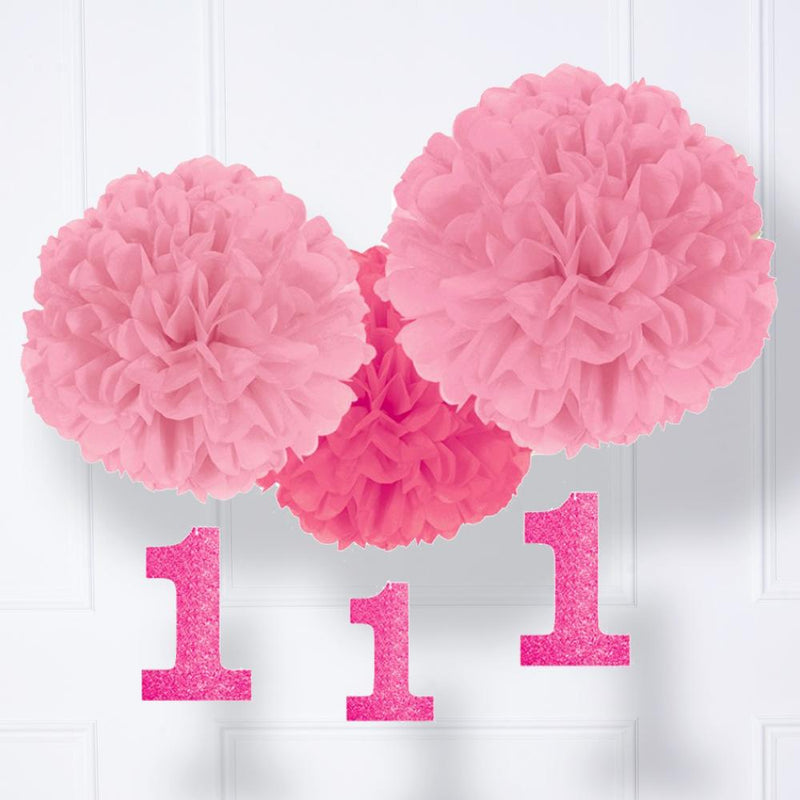 A set of 3 fluffy pink paper party pom poms for a 1st birthday