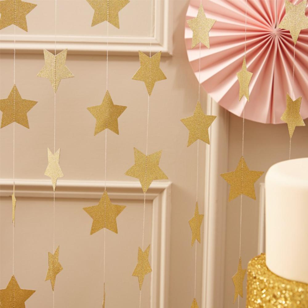 A party garland curtain made up of glittering gold stars hung over a party table