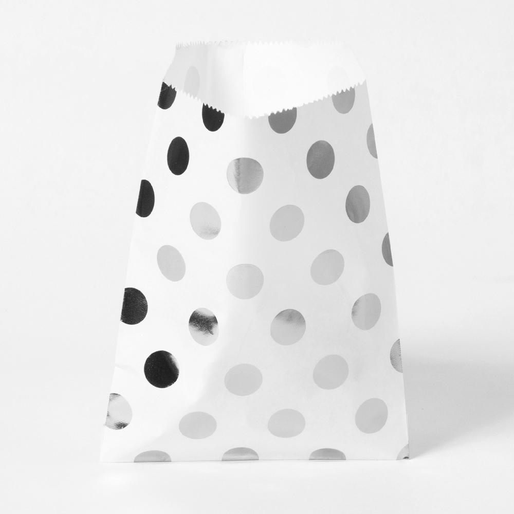 A white paper party bag with silver foil polkadots