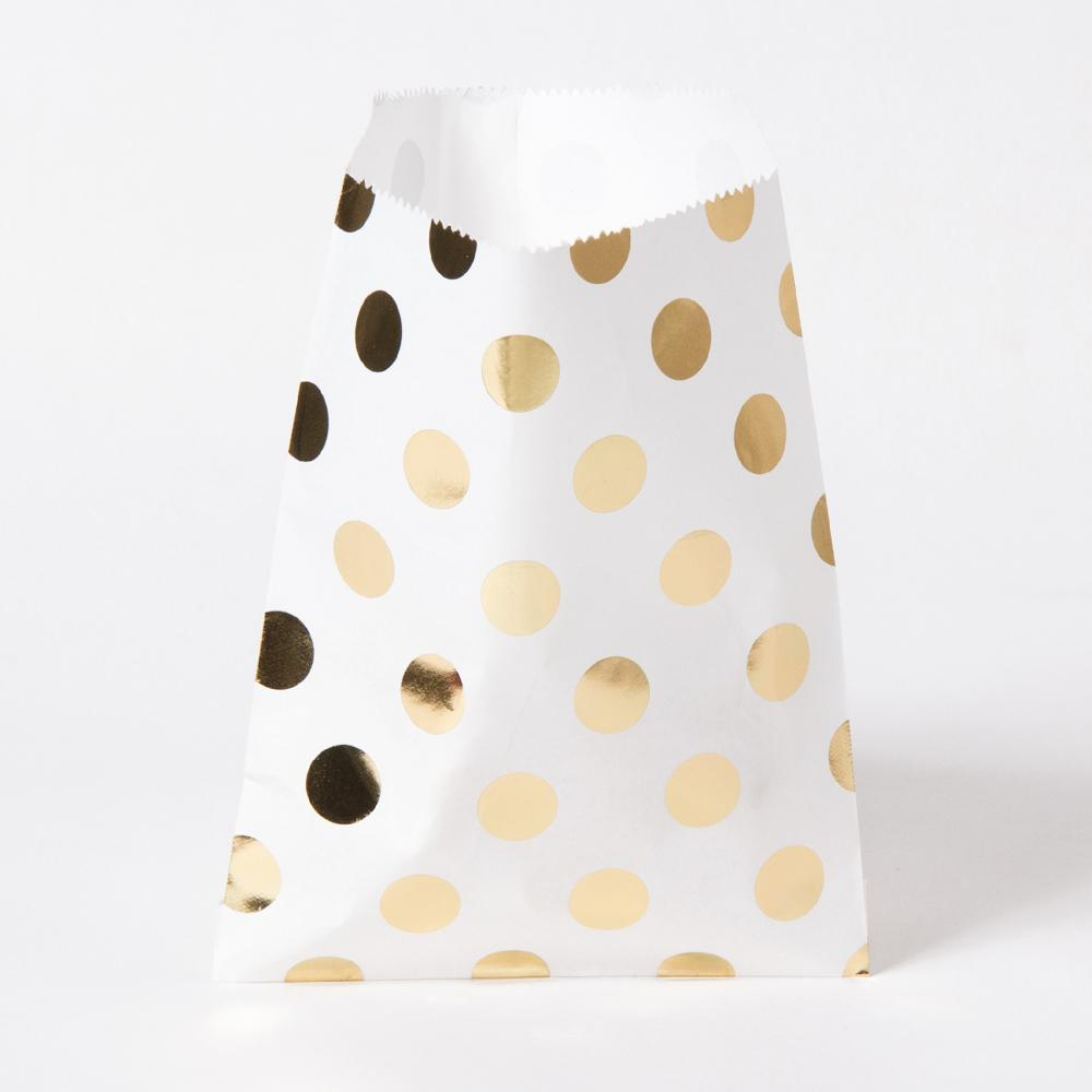 A white paper party bag with gold foil polkadots