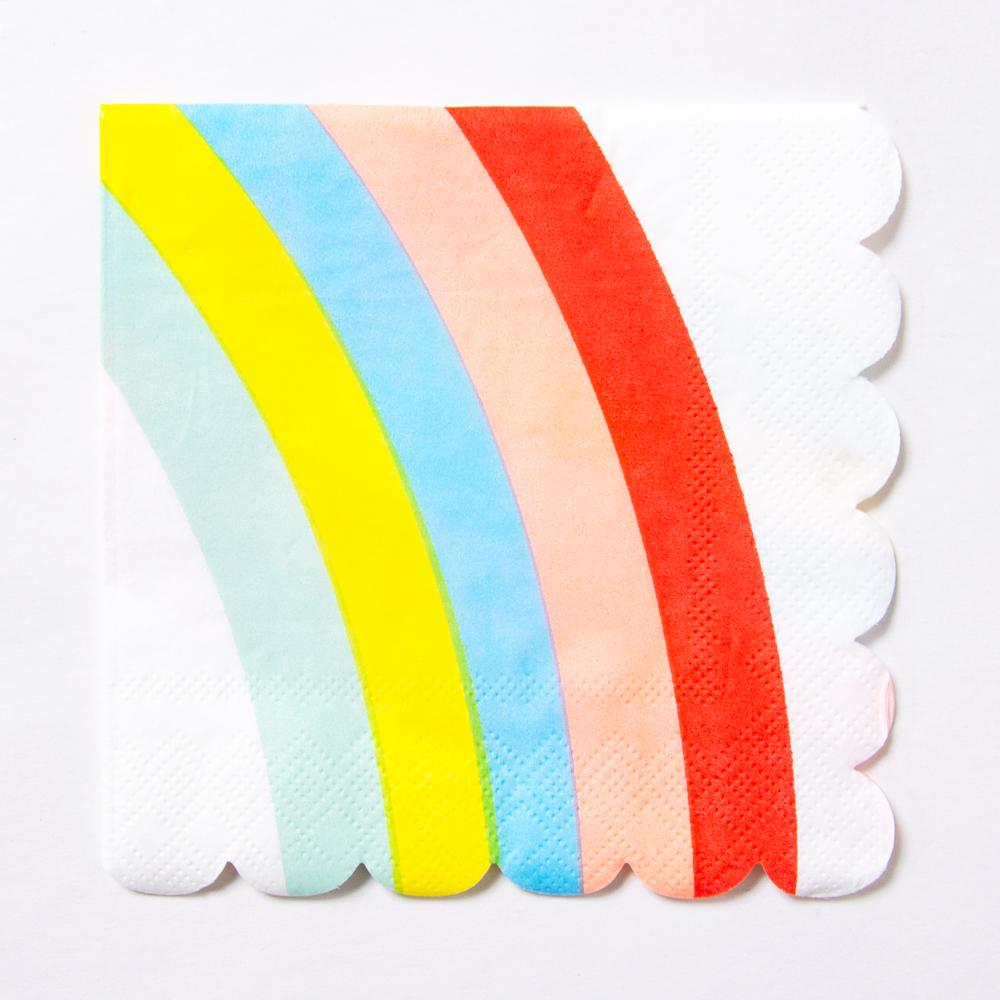 A scalloped paper party napkin with a bright rainbow design