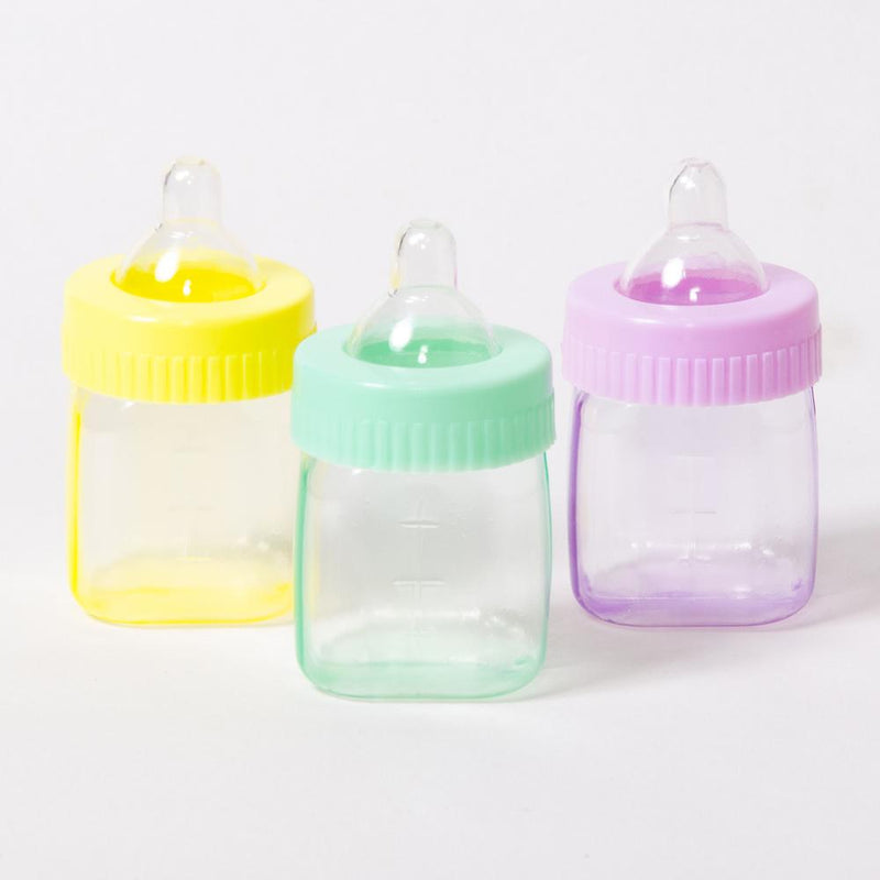 3 baby bottle-shaped baby shower sweet containers in a pink, green, and yellow colour