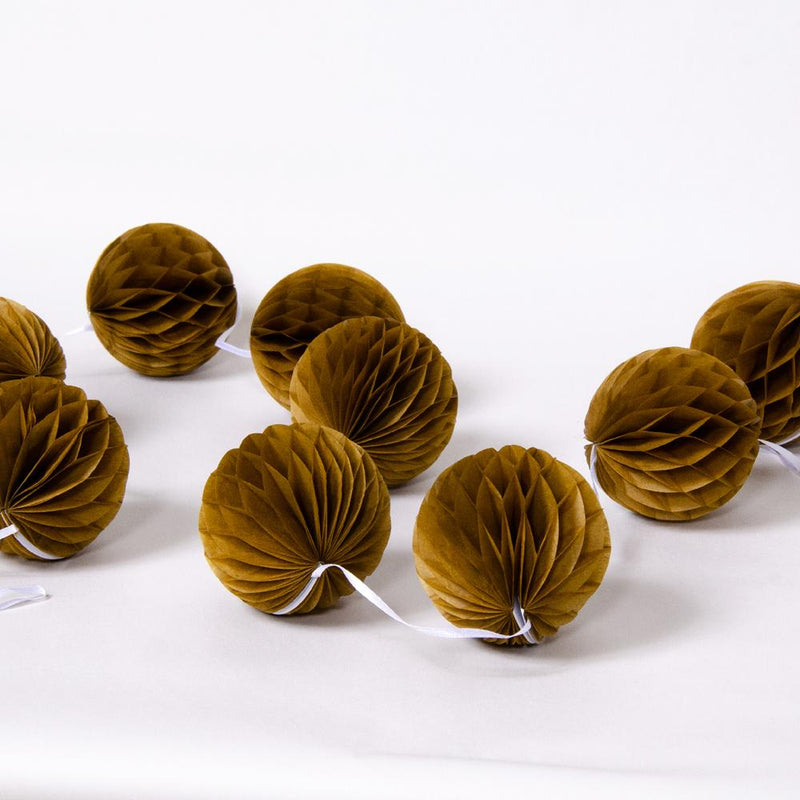 A collection of dark gold honeycomb party pom poms