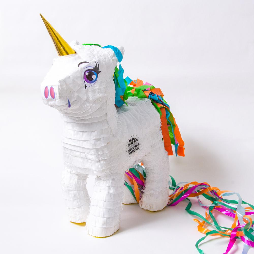 A white unicorn-shaped party pinata with colourful tassels and a gold foil horn