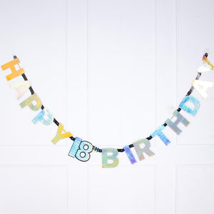 "A gold foil 18th birthday letter banner featuring a ""Happy Birthday"" phrase"