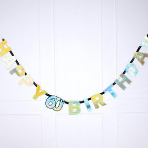 "A 60th birthday banner with a glimmery gold shimmer and a ""Happy Birthday"" phrase"