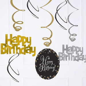 A collection of dangling gold, silver, and black ceiling decorations with happy birthday phrases
