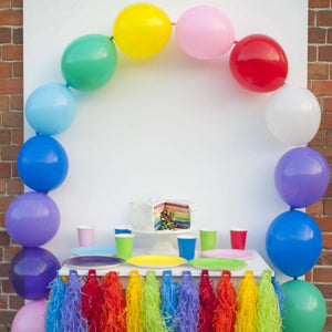 A latex balloon arch set up over a party table