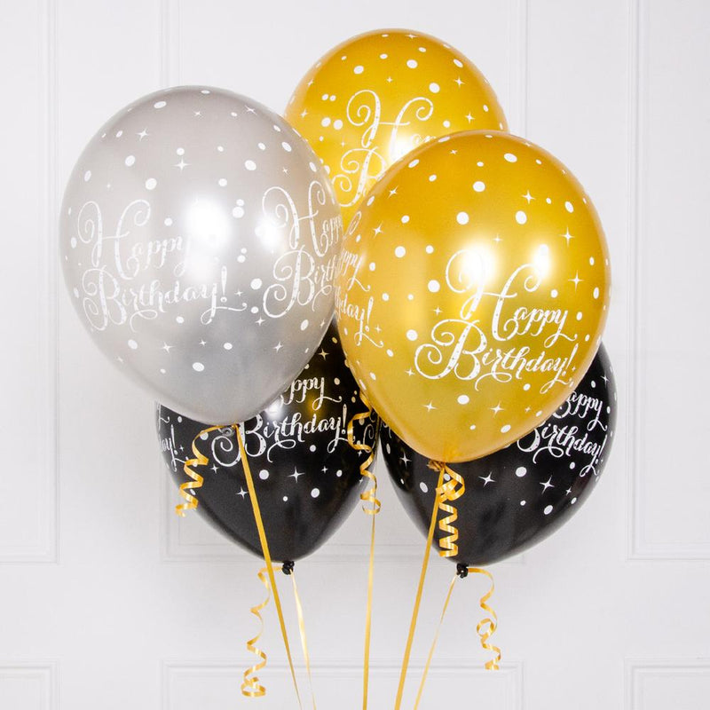 A collection of gold, black, and silver milestone birthday balloons with white printed text