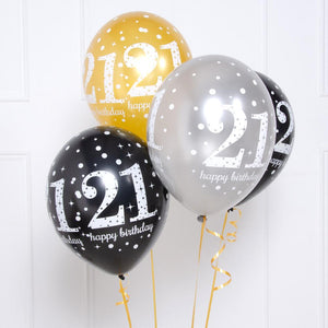 A collection of 21st birthday latex balloons in gold, black, and silver colours