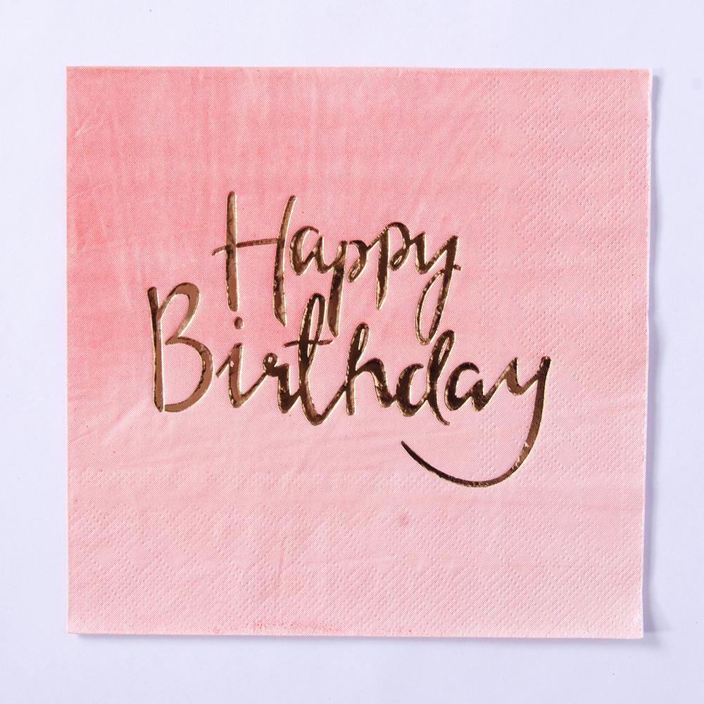 "A pink pastel-coloured party napkin with the phrase ""Happy Birthday"" written on in gold foil writing"