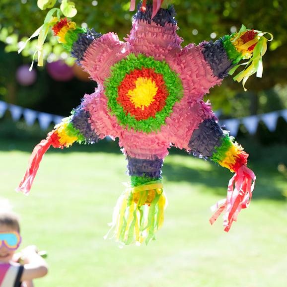 A child breaking open a classic, mexican-styled party pinata